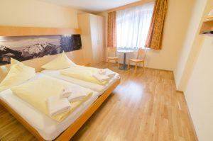 Doppelbett im Doppelzimmer im JUFA Hotel Montafon mit Kleiderschrank. Der Ort für erholsamen Familienurlaub und einen unvergesslichen Winter- und Wanderurlaub.